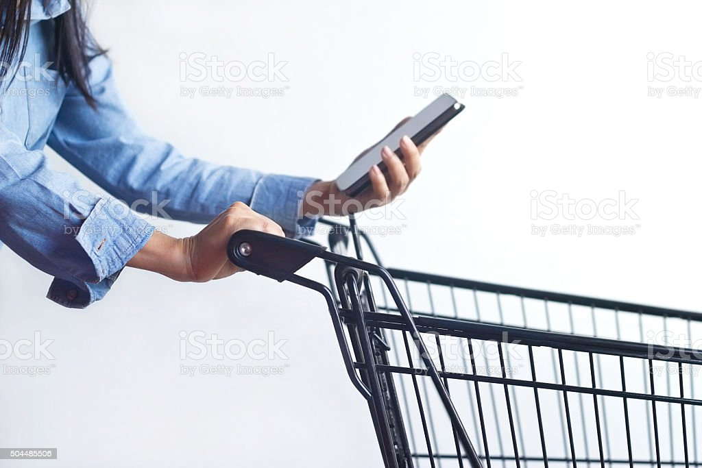 woman with shopping cart and shopping list in smartphone stock photo