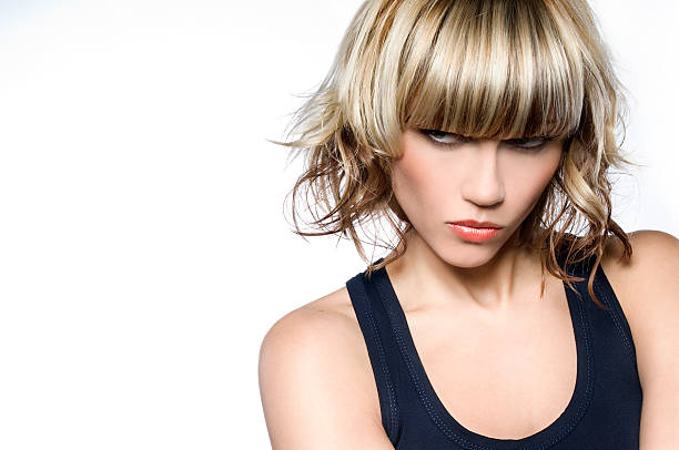 Woman with short blond hair with a mean look on her face Portrait of fashion model with trendy hairstyle highlights hair stock pictures, royalty-free photos & images