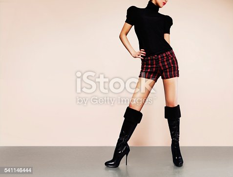 636803682 istock photo Woman with shorts with black heels boots. Fashion image. 541146444