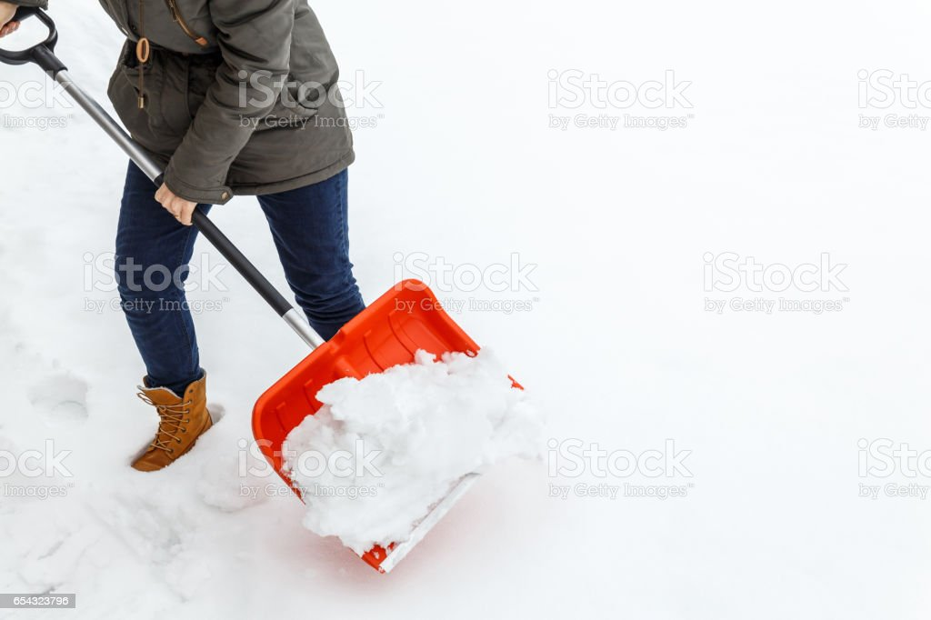 Woman with shovel cleaning winter snow. stock photo