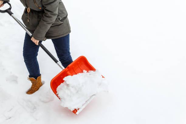 婦女用鏟子清洗冬雪。 - 鏟 個照片及圖片檔