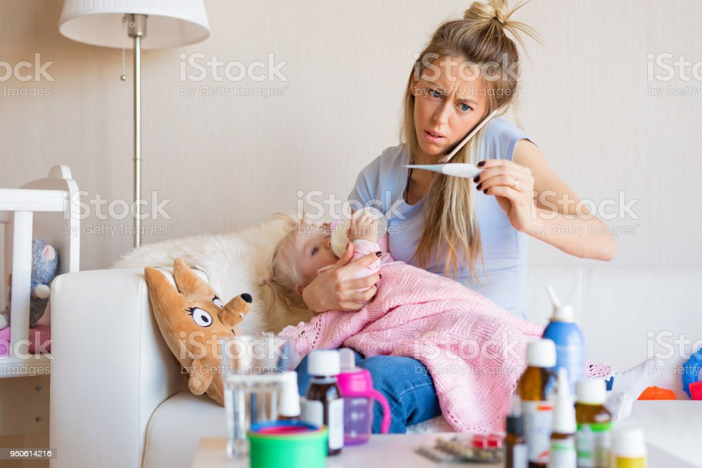 Woman with sick baby calling doctor stock photo