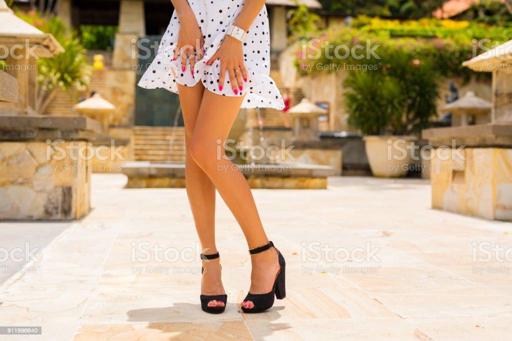 Frau mit schlanken sexy Beinen posiert in weißen Sommerkleid und schwarzen high heels – Foto