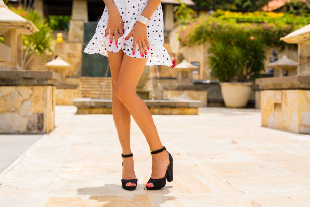 woman with slim sexy legs posing in white summer dress and black high heels - skirt stock photos and pictures