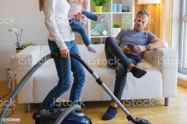 Vrouw Met Kleine Kind Doen Van Huishouden Terwijl Man Zit In De Bank Stockfoto en meer beelden van Aan het werk