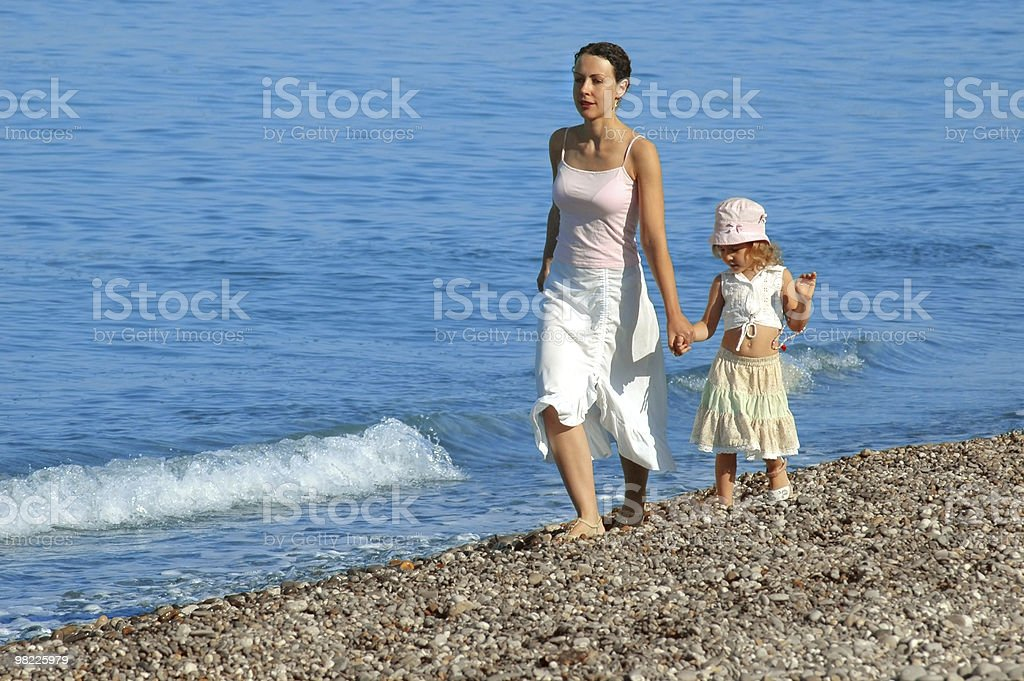 Woman with small girl go on seaside royalty-free stock photo