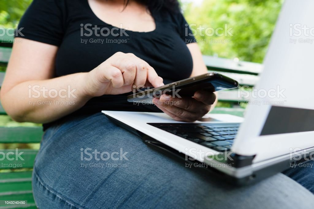woman with smart phone and laptop working outdoors stock photo