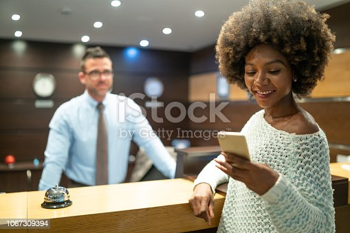 istock Woman with smart phone at hotel's reception 1067309394