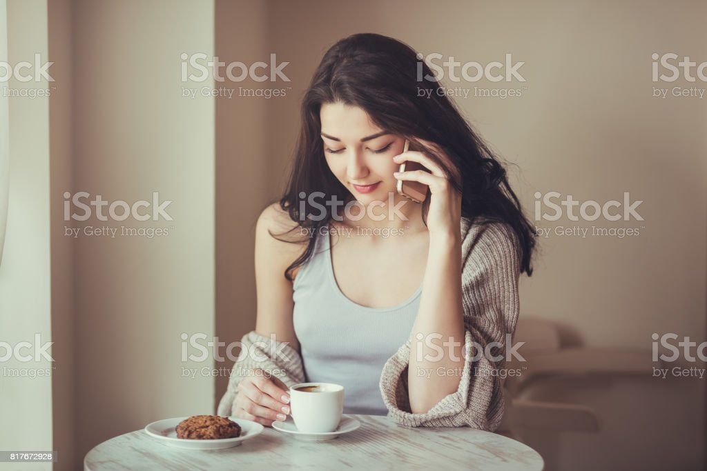 Woman with smart phone in cafe stock photo