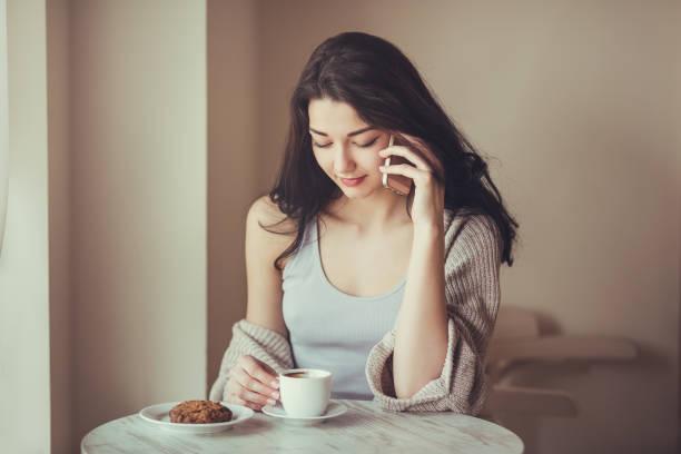 カフェでスマート フォンを持つ女性 ストックフォト