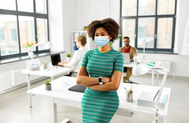 Frau mit Smart-Uhr in medizinischer Maske im Büro – Foto