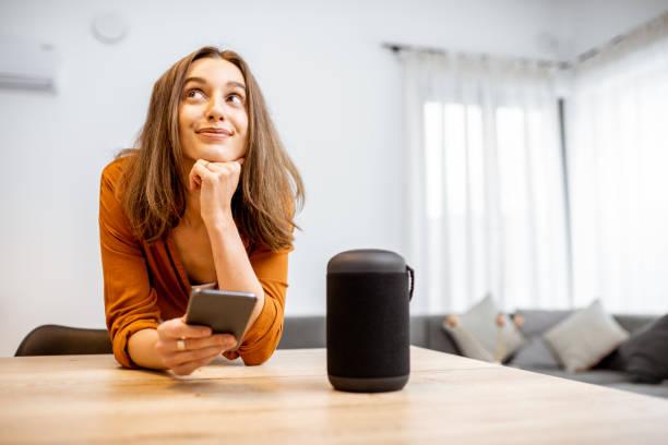 Vrouw met slimme draadloze kolom thuis foto