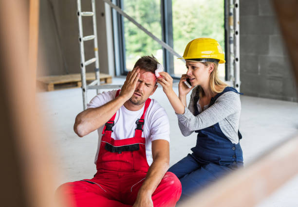 A woman with smartphone helping man worker after an accident at the construction site. stock photo