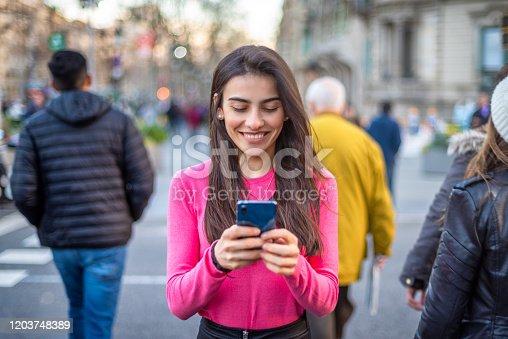 Woman with smartphone in Passeig de Gracia, Barcelona. Spain