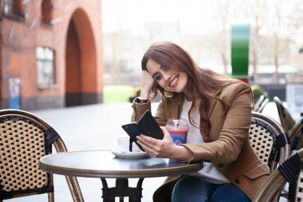 Woman with smartphone outside cafe stock photo