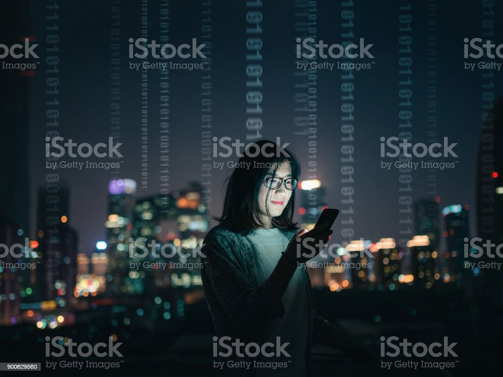 Woman with Smartphone Standing on Skyscraper Roof stock photo