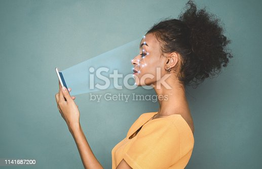 851960142 istock photo Woman with smartphone using face ID recognition system 1141687200