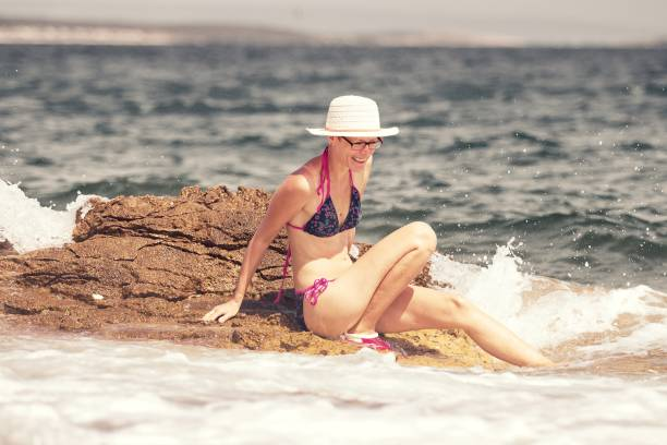 Woman with smile and hat sitting on the rock in the sea stock photo