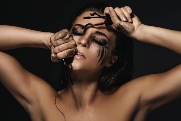 frau mit flecken von make-up auf dem gesicht und gebrochenen mascara-bürsten - anti unordnung stock-fotos und bilder