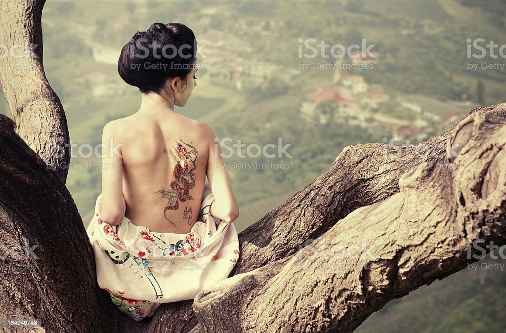 Woman with snake tattoo on the tree branch stock photo