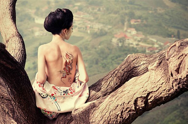 woman with snake tattoo on the tree branch - geisha girl stock photos and pictures