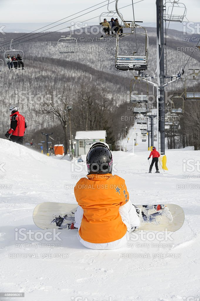 Woman with Snowboard Sitting at Top of Ski Slope stock photo