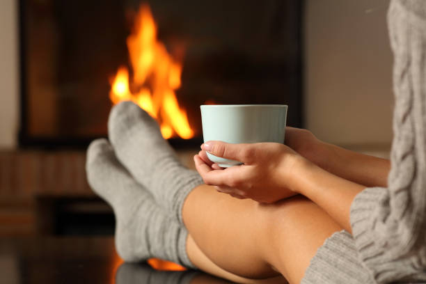 Woman with socks holding coffee in a fireplace stock photo