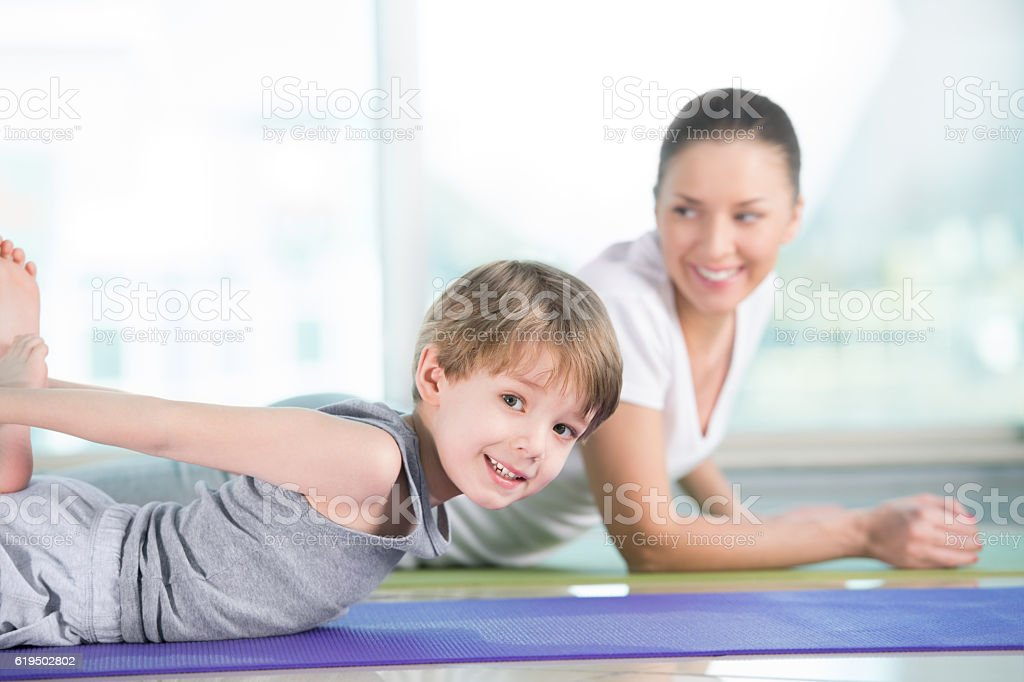 Woman with son doing gymnastic exercise stock photo