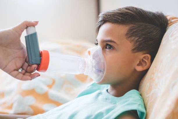 vrouw met zoon inhaleren met vernevelaar thuis doen - ventilator bed stockfoto's en -beelden