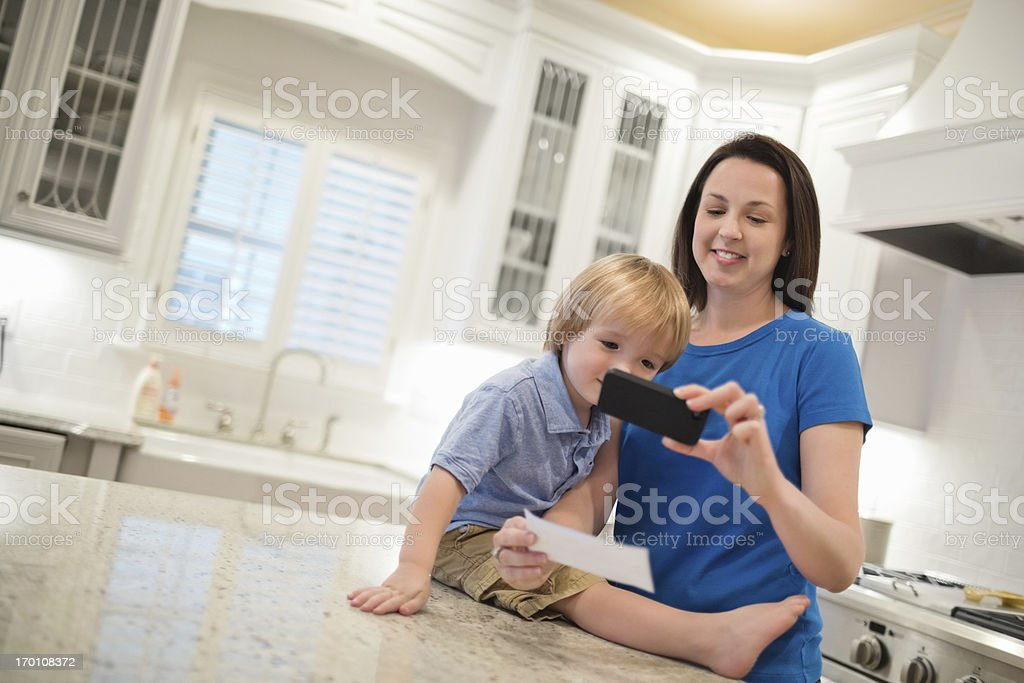 Woman With Son Using Smart Phone To Deposit Check royalty-free stock photo