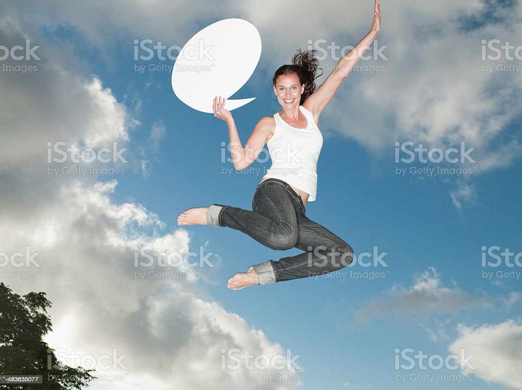 Woman with speech balloon leaping outdoors with blue sky and clouds stock photo
