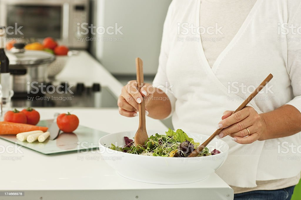 Woman with spoon mixing raw vegetables in bowl royalty-free stock photo