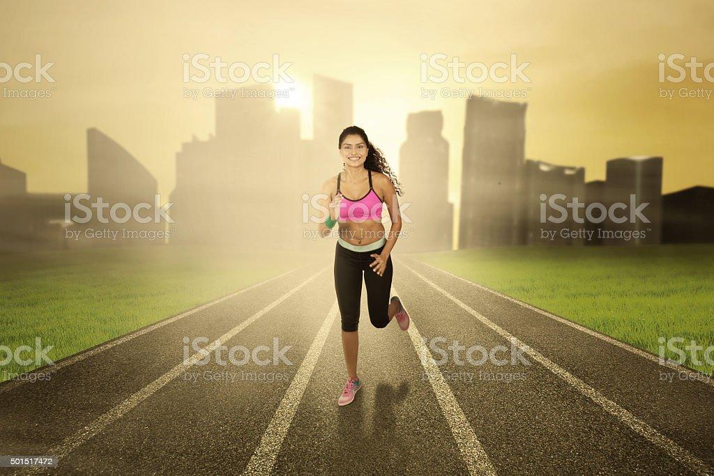 Woman with sportswear runs at field stock photo