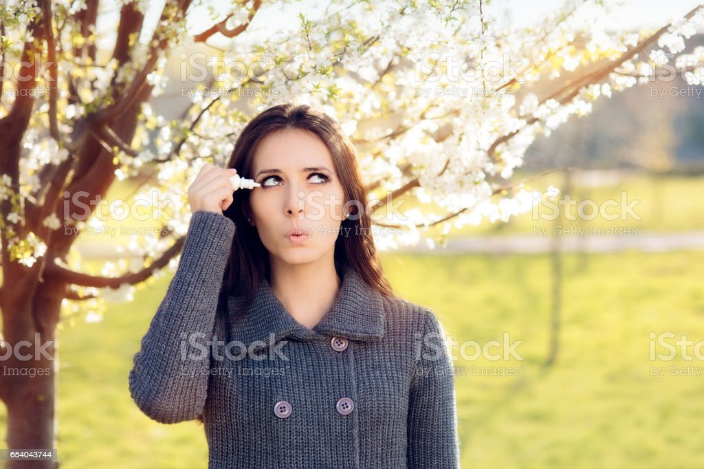 Woman with Spring Allergies Using Eye Drops stock photo
