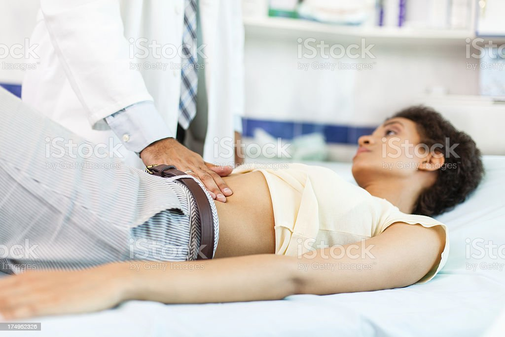 Woman with stomachache on medical exam stock photo