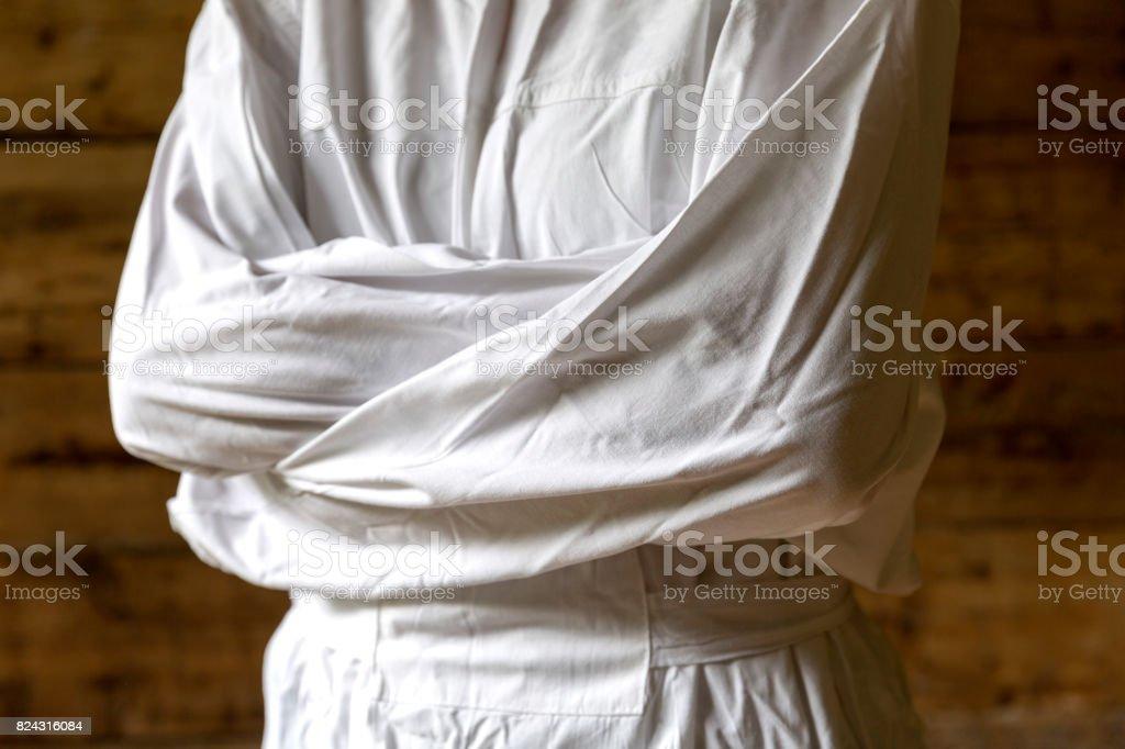 Woman with straitjacket, dark background stock photo