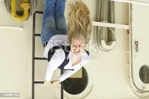 istock Woman with striking blond hair hanging off a boat ladder 140382763