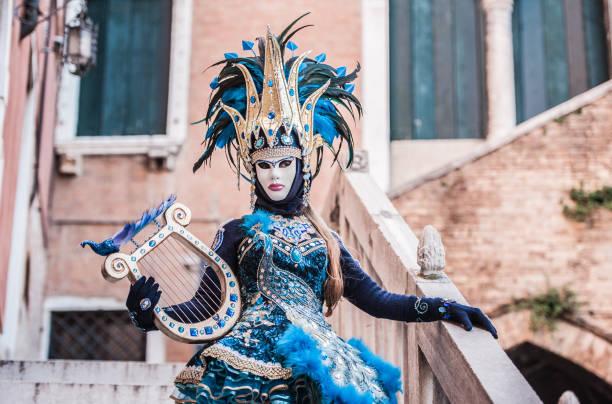 Frau mit Saiteninstrument in attraktiven goldenen und blauen Kostüm im Karneval von Venedig – Foto