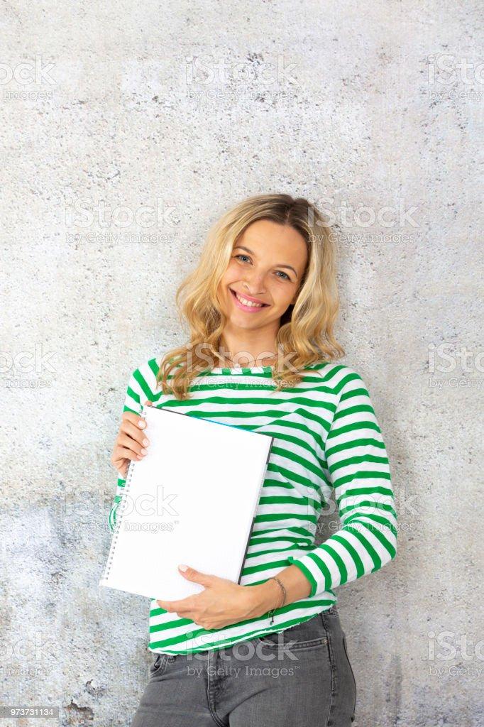 Frau mit gestreiften Pullover hält leerer Block oder Note pad – Foto