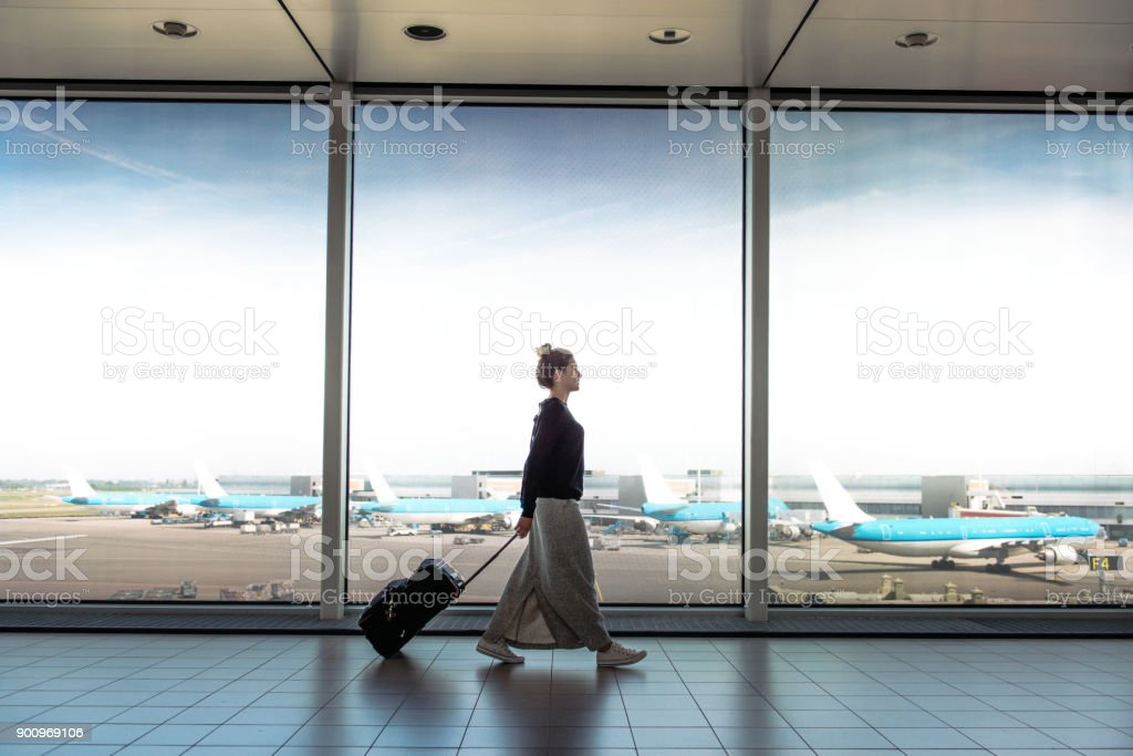 Woman with suitcase is going to board on the next flight stock photo