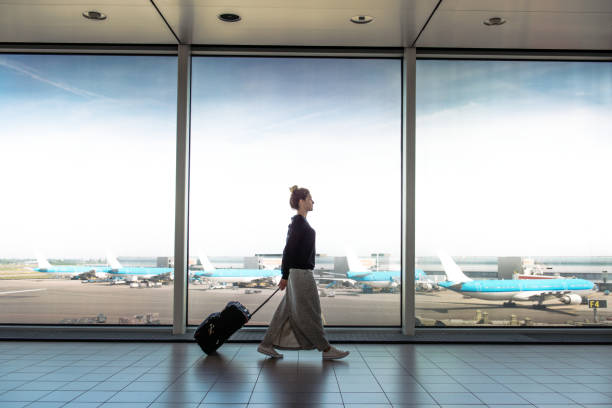 woman with suitcase is going to board on the next flight - airport check in counter stock pictures, royalty-free photos & images