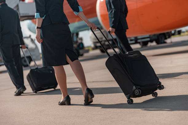 Woman with suitcase is ready for flight Young stewardess walking in airport stock photo. Airways concept cabin crew stock pictures, royalty-free photos & images