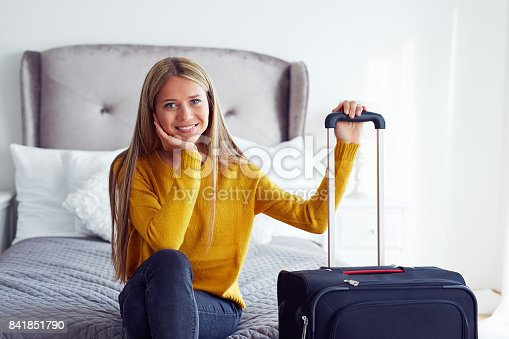 istock Woman with suitcase sitting on bed 841851790