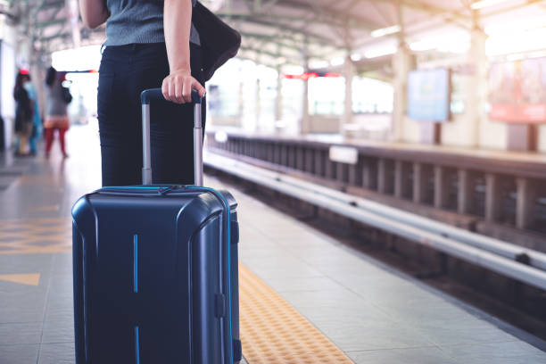 Woman with suitcase waiting for a train in modern station platform Woman with suitcase waiting for a train in modern station platform pasport malaysia stock pictures, royalty-free photos & images