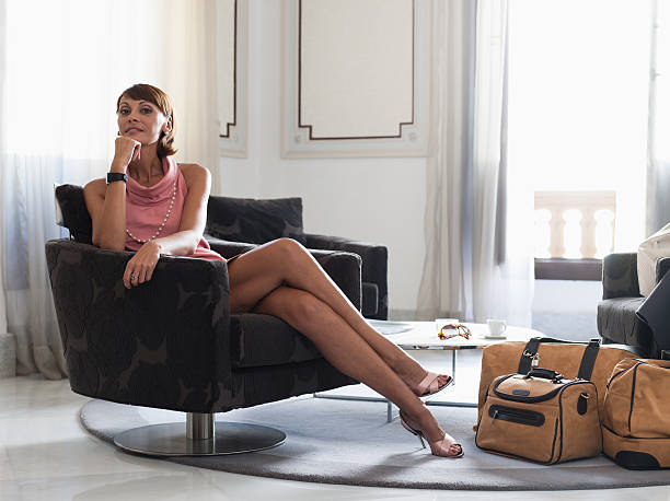 woman with suitcases sitting in waiting area - exploitation stock photos and pictures