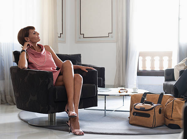 Woman with suitcases sitting in waiting area stock photo
