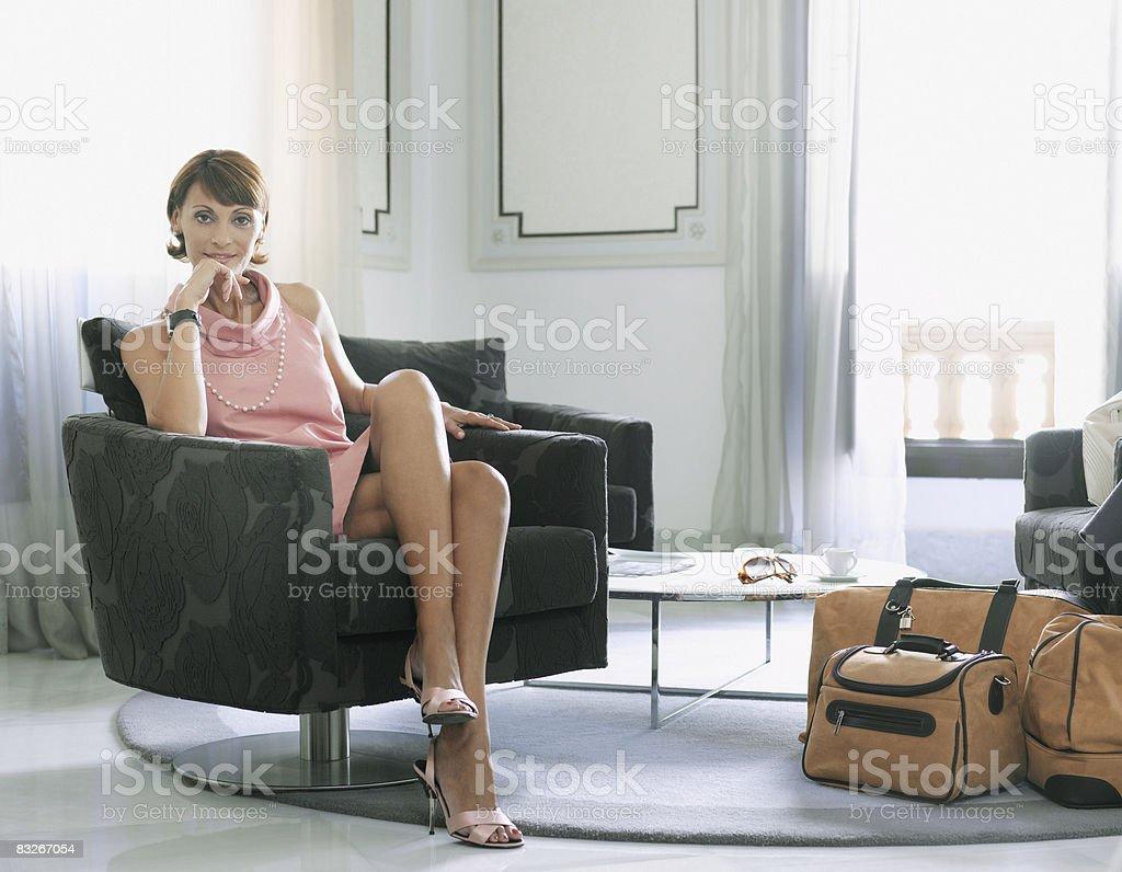Kobieta z walizki siedzi w poczekalni zbiór zdjęć royalty-free