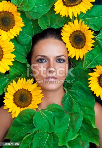 Beautiful women with sunflower and leaves