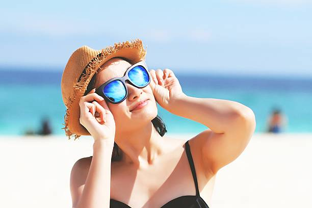 Woman with sunglasses in bikini, Sunglasses reflects the sun. stock photo