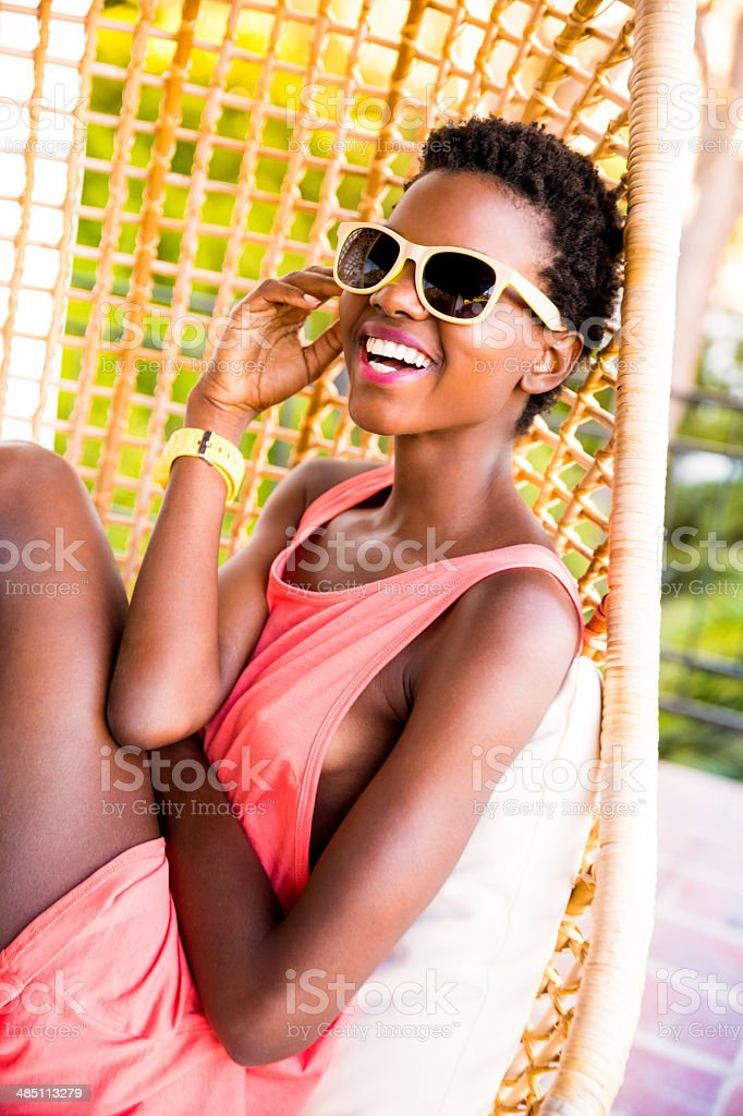 Woman with sunglasses sitting in hanging chair stock photo